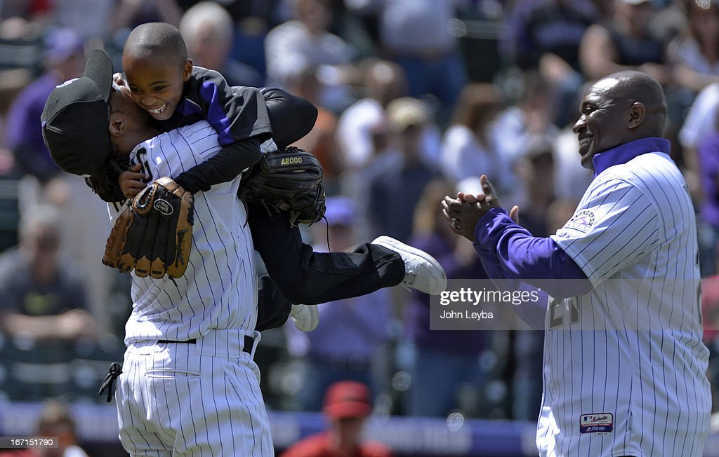 Colorado Rockies retired player Eric Young (R) looks on as stands Dallas Young 6-years-old jumps in the arms of his older brother Eric Young Jr. after throwing out the first pitch prior to their game against the Arizona DiamondBacks April 21, 2013 at Coors Field.