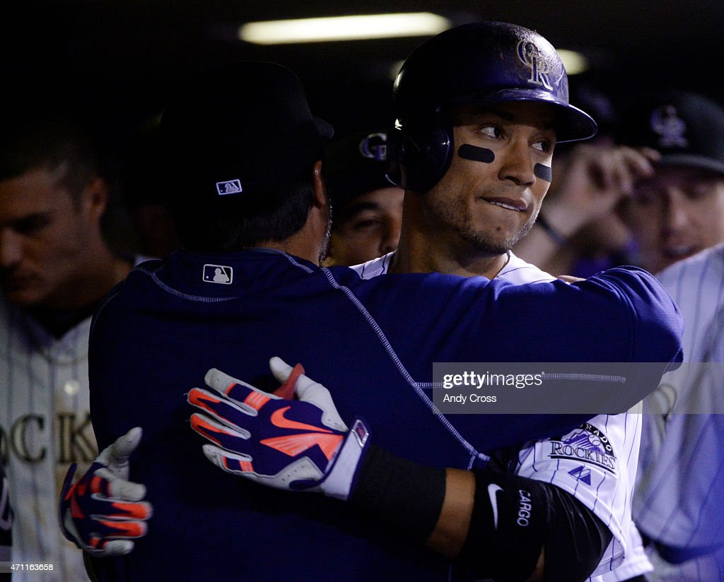 Colorado Rockies right fielder Carlos Gonzalez hugs special assistant coach Vinny Castilla in the dugout after hitting a solo home run against the...