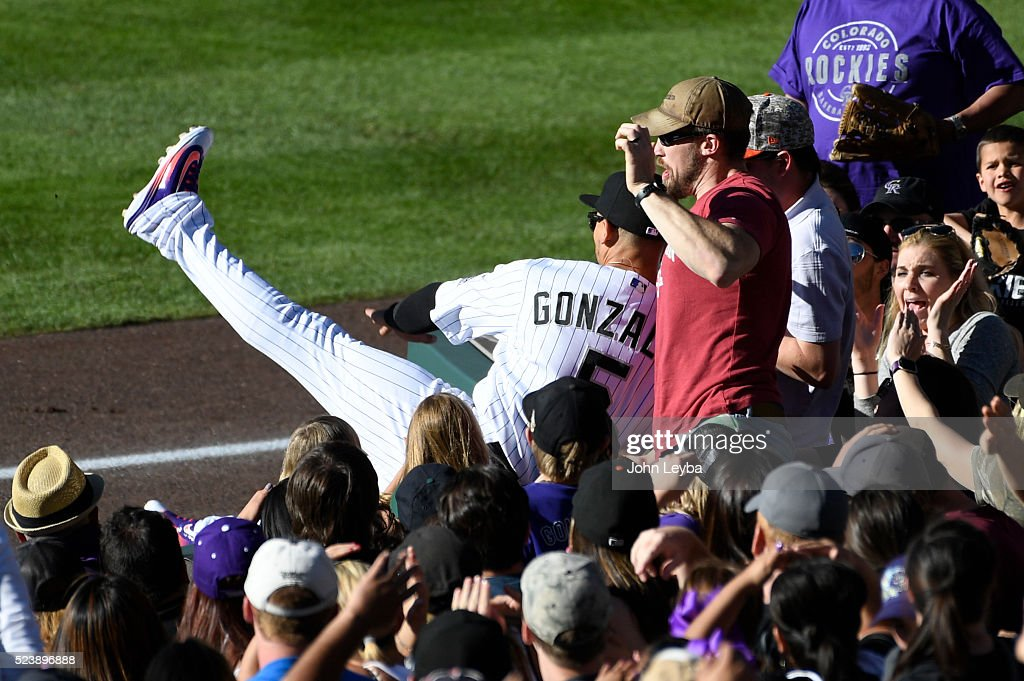 Colorado Rockies right fielder Carlos Gonzalez (5) tracks down a high fly ball in foul territory hit by Los Angeles Dodgers catcher Yasmani Grandal (9) in the 9th inning against the Colorado Rockies April 24, 2016 at Coors Field. Gonzalez made an attempt to catch the ball and flipped in to the stands and missed the ball.