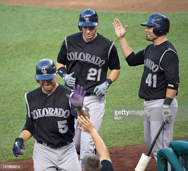 Colorado Rockies right fielder Tyler Colvin and Carlos Gonzalez are greeted by Colorado Rockies catcher Wil Nieves at the dugout after Colvin a...