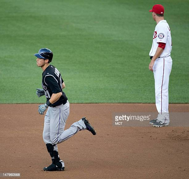 Colorado Rockies right fielder Tyler Colvin rounds the bases in front of Washington Nationals second baseman Danny Espinosa after hitting a home run...
