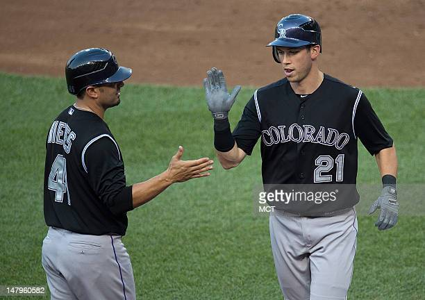 Colorado Rockies right fielder Tyler Colvin slaps hands with Wil Nieves after hitting a home run off Nationals starting pitcher Stephen Strasburg...