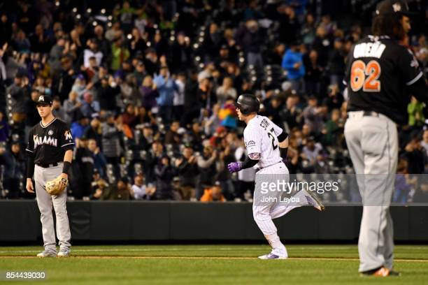 Colorado Rockies shortstop Trevor Story heads home after his homer to center field scoring third baseman Nolan Arenado and first baseman Mark...