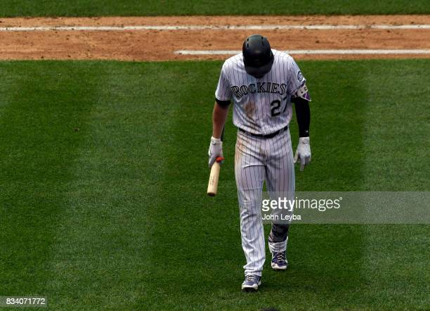 Colorado Rockies shortstop Trevor Story walks off the field with his head down after striking out in the ninth inning to end the game against the...