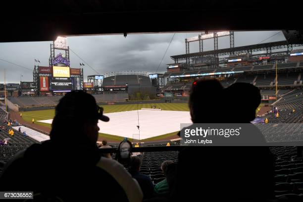 Colorado Rockies sit under the overhang as the ground crew covers the infield due to rain before the game with the Washington Nationals on April 25...