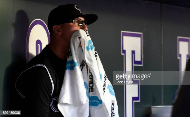 Colorado Rockies starting pitcher Jeff Hoffman sits in the dugout with a towel over his mouth after he was taken out of the game by Bud Black in the...