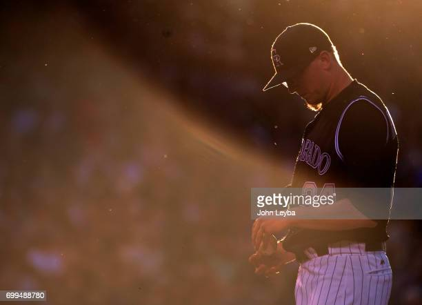 Colorado Rockies starting pitcher Jeff Hoffman stands on the mound with his head down as manager Bud Black comes out to pull him from the game in the...