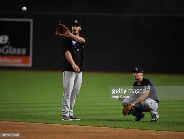 Colorado Rockies third baseman Nolan Arenado left and Colorado Rockies catcher Tony Wolters retrieving baseballs during practice at Chase Field...