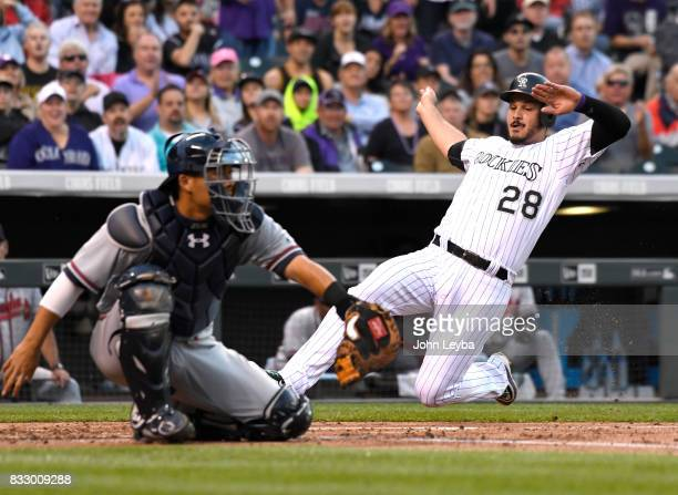 Colorado Rockies third baseman Nolan Arenado slides in at home safe on a Mark Reynolds single in the first inning against the Atlanta Braves on...