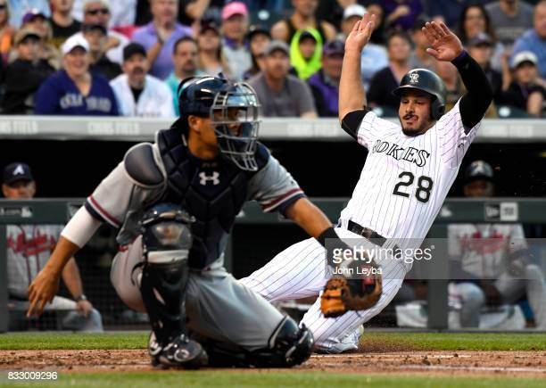 Colorado Rockies third baseman Nolan Arenado slides in at home safe on a Mark Reynolds single in the first inning under the glove of Atlanta Braves...