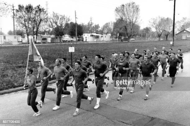 Colorado State Patrol recruits prepare for the Kops 'n Kids race by doubletiming in formation down on of the streets of camp George West in Golden...