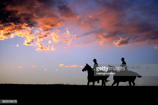 Colorado sunset silhouette horseback riders copy space