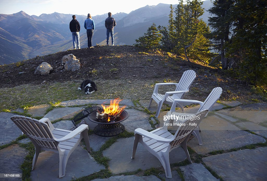 USA, Colorado, Three people standing near fire pit looking at landscape  : Stock Photo