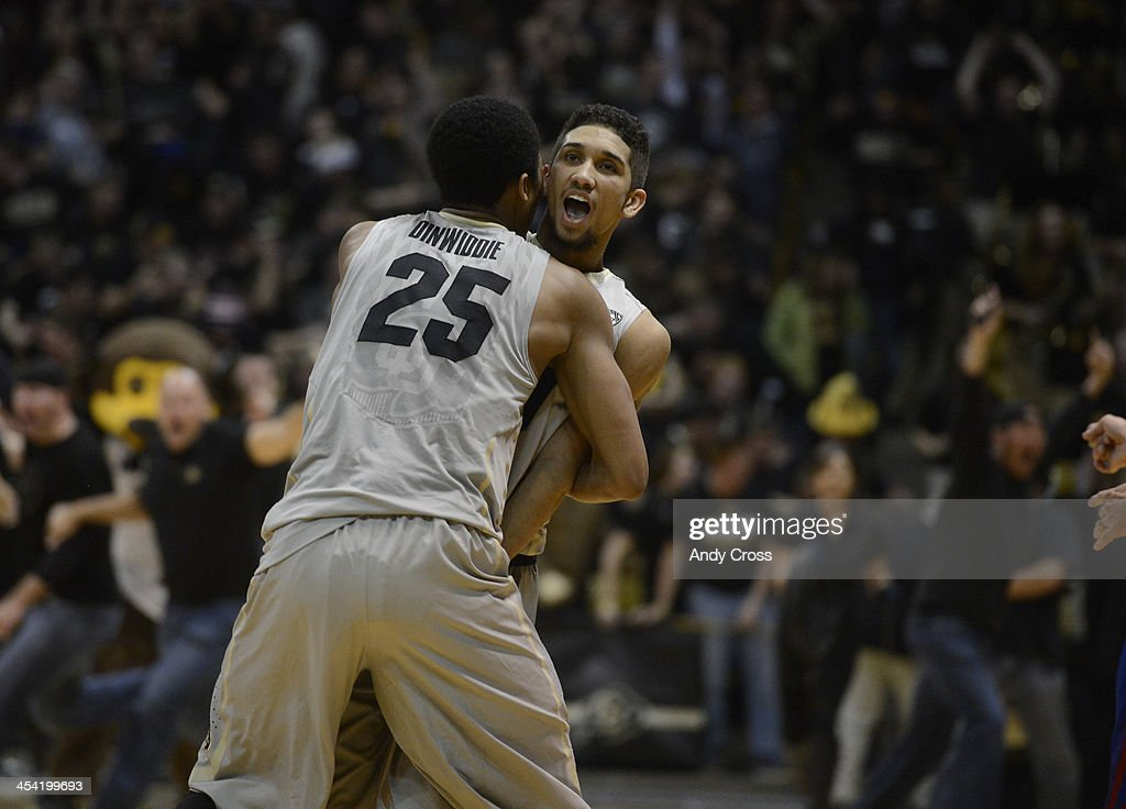 Colorado University guard, Askia Booker, right, stands in place, shocked that he sunk a three-pointer on the last shot of the game to win against the Kansas Jayhawks 75-72 at the Coors Events Center in Boulder Colorado Saturday afternoon, December 07, 2013. CU teammate, Spencer Dinwiddie, left, charges Booker to celebrate.