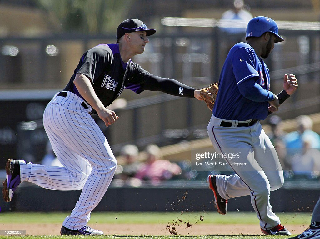 Coloraodo Rockies shortstop Troy Tulowitzki (2) tags out the Texas Rangers' Elvis Andrus, caught between first base and second base in the first inning of a spring training game in Scottsdale, Arizona, Monday, February 25, 2013. The Rockies beat the Texas Rangers 9-1.