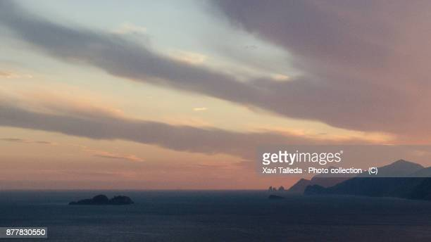 A colored and cloudy sunset over the tyrrhenian sea with the Faraglioni stacks at background