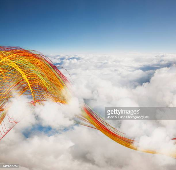 Colored cables swirling through clouds