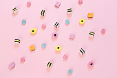 Jelly colored candy scattered on the pink background, abstract background concept