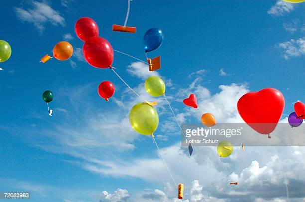Colored helium balloons with messages floating in the sky above
