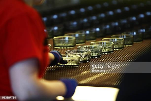 Colored Kastehelmi style glass bowls move along a conveyor belt following manufacture at the Iittala Oyj glass factory operated by Fiskars Oyj in...