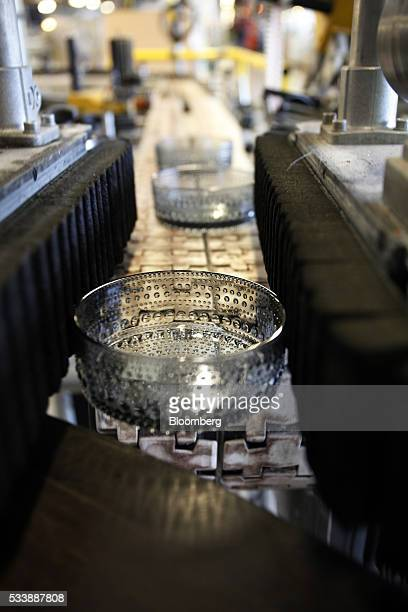 Colored Kastehelmi style glass bowls move along a conveyor belt following manufacture in the workshop at the Iittala Oyj glass factory operated by...