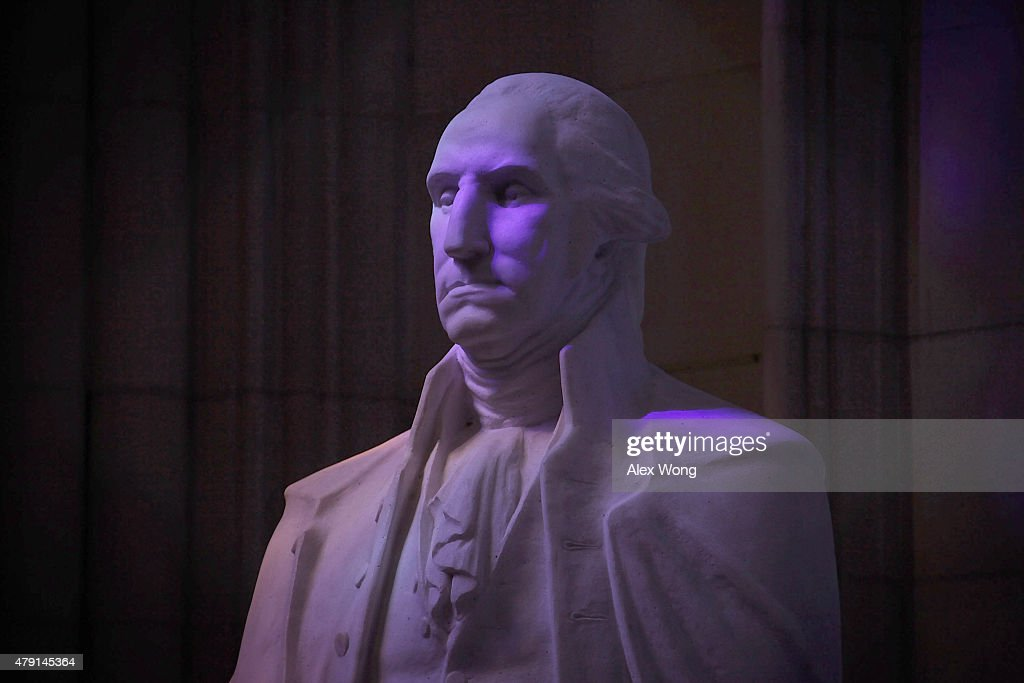 Colored lights shine through stained glass windows onto a statue of George Washington at the National Cathedral July 1 2015 in Washington DC The...