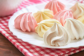 Fresh delicious colored meringue cookies served on white plate