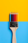 Two photographs of colored pencils and a paint brush combined to form a new object.
