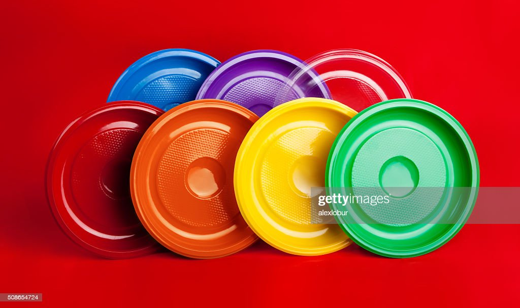 Colored plastic utensils on red background : Stock Photo