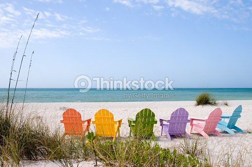 Colorful Adirondack Chairs Facing A White Sandy Beach Stock ...