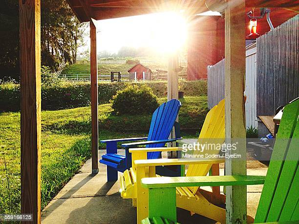 Colorful Adirondack Chairs In Back Yard Of House