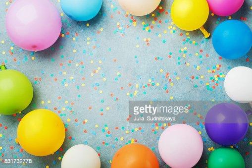 Ballons colorés et des confettis sur le dessus de table turquoise Découvre. Fond d'anniversaire, de vacances ou de parti. Style plat laïc. : Photo