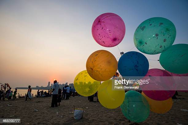 Colorful balloons for sale at the crowded Marine Drive Beach at sunset