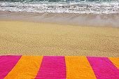 Colorful beach towel on sandy beach, ocean background.