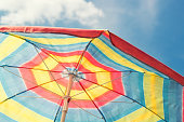 Colorful beach umbrella yellow, red, blue against blue sky, vintage filter