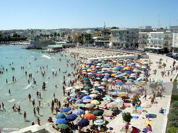 CONTENT] Colorful beach umbrellas and a lot of tourists at the seaside in Otranto during the summer holidays