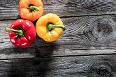 vegetable still life - variety of colorful bell peppers on authentic old wooden background or barn table for vegetarian diet, studio shot, top view