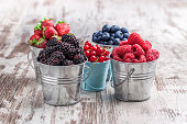 Colorful berries assortment in five tin cans on rustic wooden table blueberry, raspberry, red currant, strawberry, in five old tin cans on rustic wooden table in studio