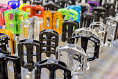 Many colorful bicycle pedals on store shelve.