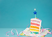 Slice of  birthday cake on a blue background with colorful layers and candle.