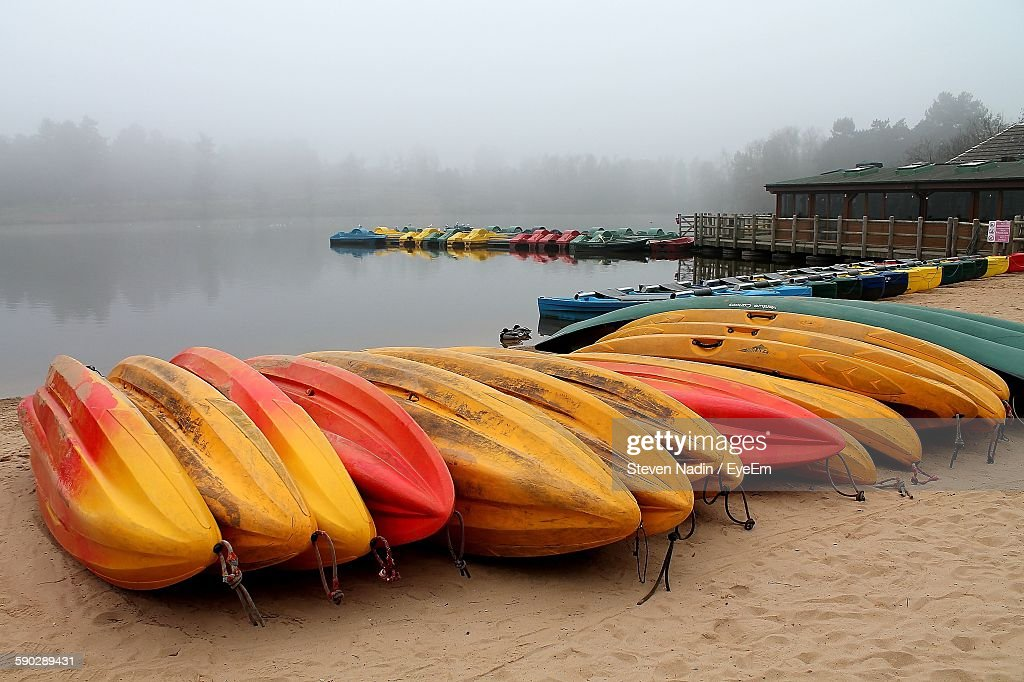Colorful Boats Moored By Lake During Foggy Weather