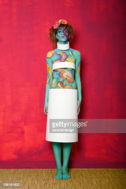 Colorful Body Painted Woman Posing Against Pink Wall