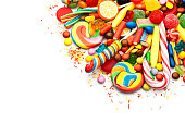 Top view of colorful candies and jellybeans heap arranged at the top corner of a white background leaving a useful copy space for text and/or logo . DSRL studio photo taken with Canon EOS 5D Mk II and