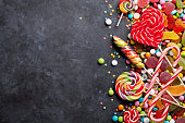 Colorful candies, jelly and marmalade over stone background. Top view with copy space
