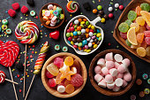 Colorful candies, jelly and marmalade on stone background. Top view