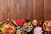 Colorful candies, jelly and marmalade on wooden background. Top view with copy space
