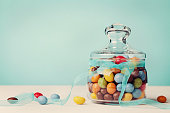Colorful candy jar decorated with bow ribbon against blue background, gifts for Birthday or Easter