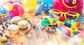 Colorful carnival or party background with donuts, balloons, streamers and confetti and funny face formed from wig, nose and glasses on rustic wooden planks with copy space