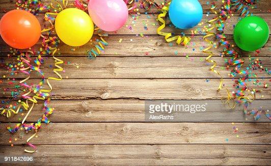 Coloré cadre carnaval ou la fête des ballons, serpentins et confettis sur une planche en bois rustique : Photo