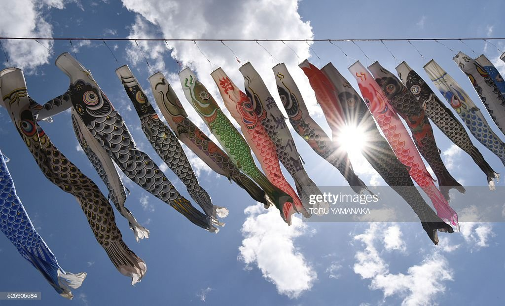 Colorful carp streamers flutter above a riverside park in Sagamihara, suburban Tokyo, on April 29, 2016 ahead of May 5 Children's Day in Japan. Some 1,200 carp streamers were hoisted over the Sagami River to celebrate the annual holiday of Children's Day - part of Japan's 'Golden Week' holiday which is traditionally one of the busiest travel times of the year. / AFP / TORU
